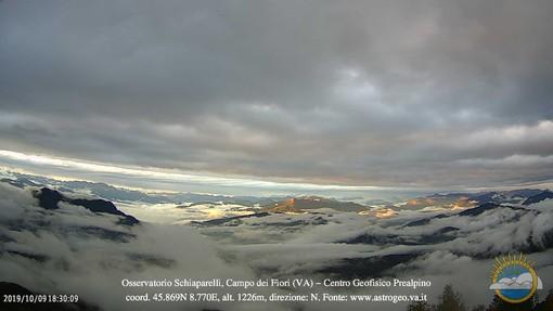 Il fantastico panorama con un doppio strato di nubi in dissolvimento sui nostri cieli catturato dalle webcam del Centro Geofisico Prealpino al Campo dei Fiori (foto tratta dalla pagina Facebook della Società Astronomica G.V. Schiapparelli)